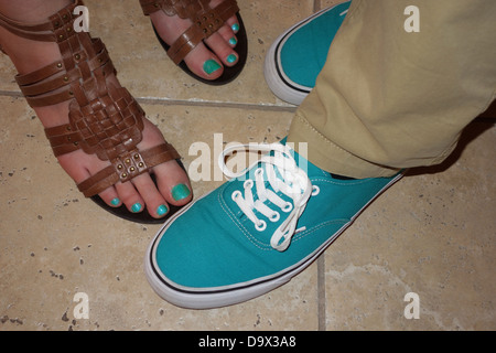 Shoes on boy with matching toenails on girl. - Stock Photo