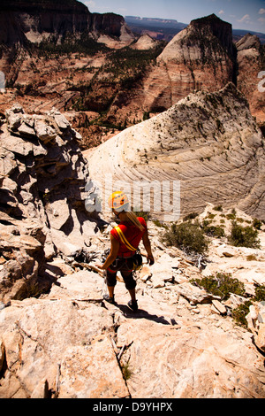 A female rock climber descends Aries Butte in Zion National Park after climbing Led by Sheep (5.7) in Springdale, - Stock Photo