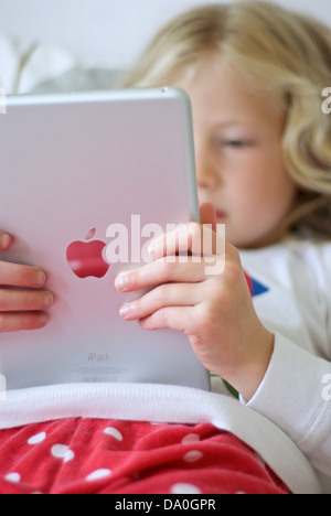 Young girl using an iPad mini - Stock Photo