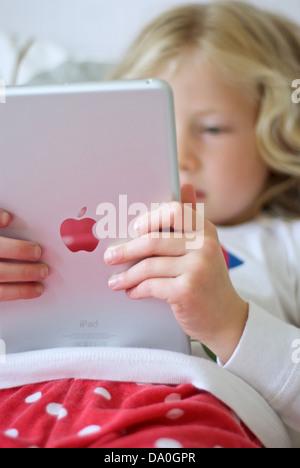 Young girl using an iPad mini - Stock Photo