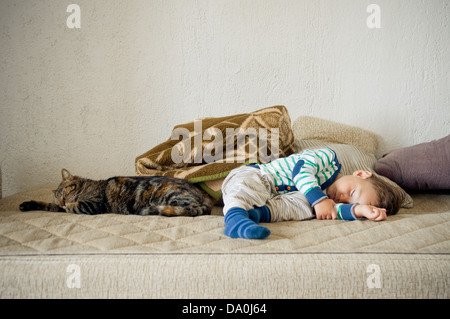 Cute baby toddler boy and cat sleeping together - Stock Photo