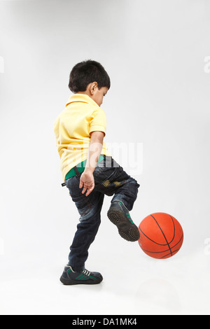 Little 5 year old  Indian kid kicking a ball. - Stock Photo