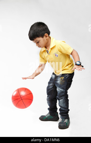 Little 5 year old  Indian kid throwing up a ball. - Stock Photo