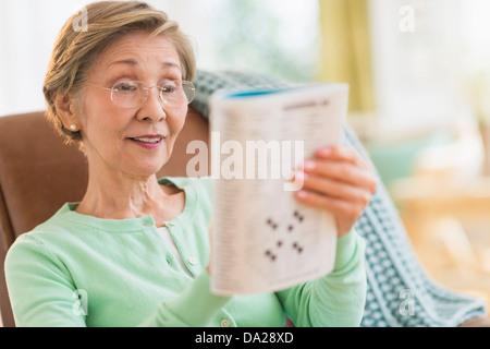 Senior woman doing crossword puzzle - Stock Photo