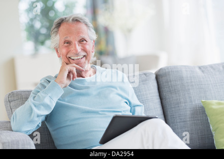 Senior man sitting on sofa with digital tablet - Stock Photo