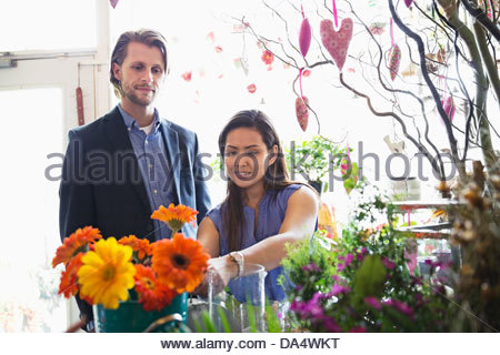 Female florist helping male customer in flower shop - Stock Photo