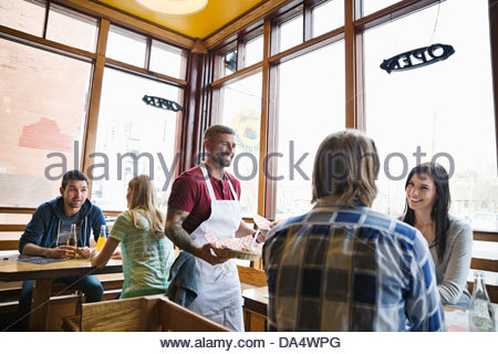 Male deli owner serving food to customers - Stock Photo