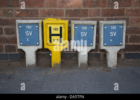 Fire hydrant water locator signage and sluice valve indicators on a UK street pavement - Stock Photo