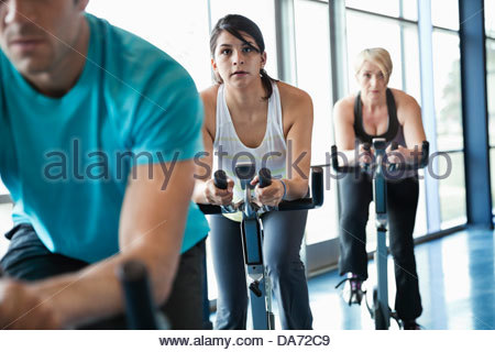 People exercising on stationary bikes in fitness class - Stock Photo