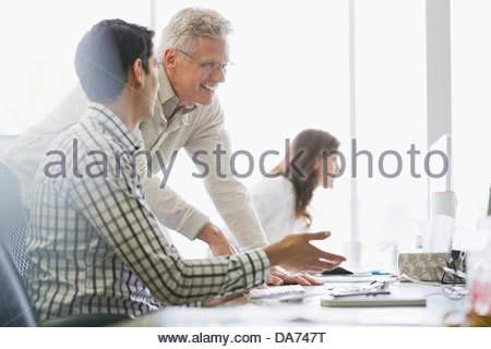 Business colleagues working on computers in office - Stock Photo