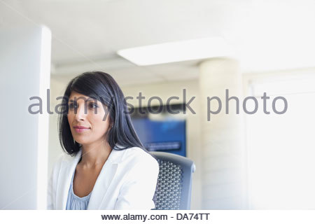 Businesswoman working on computer in office - Stock Photo