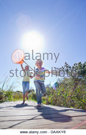 Enthusiastic boy and girl running barefoot with fishing nets - Stock Photo