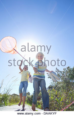 Enthusiastic boy and girl holding fishing nets - Stock Photo