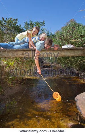 Father, daughter and son laying on footbridge and dipping fishing net in stream - Stock Photo