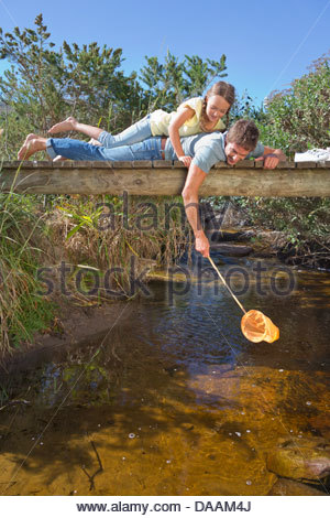 Father and daughter laying on footbridge and dipping fishing net in stream - Stock Photo