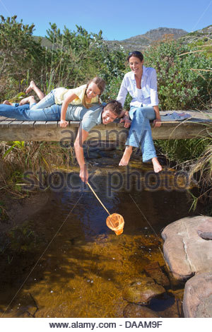 Family laying on footbridge and dipping fishing net in stream - Stock Photo