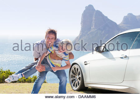 Portrait of enthusiastic father playing with son outside car near ocean - Stock Photo