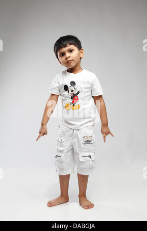 Little 5 year old Indian kid giving comic reaction - Stock Photo