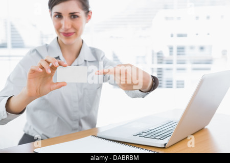 Young businesswoman pointing to blank business card - Stock Photo