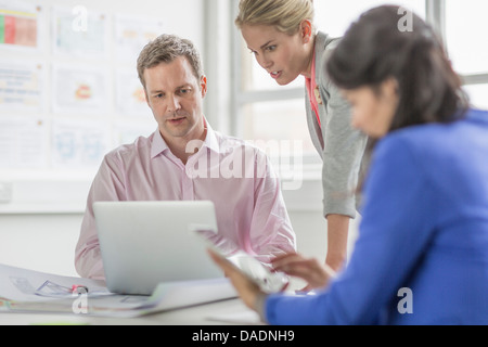 Business colleagues using laptop in meeting - Stockfoto