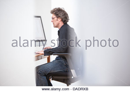 Male in an office working on computer - Stock Photo