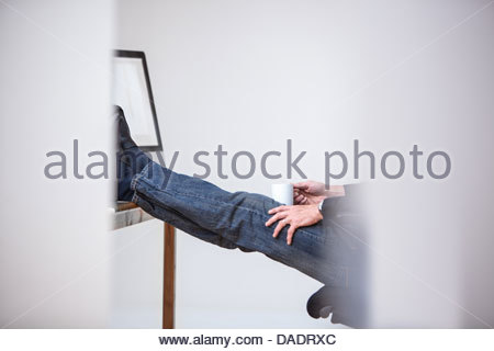 Computer operator with feet on desk and mug of coffee - Stock Photo