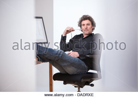 Portrait of mature male posing in office chair - Stock Photo