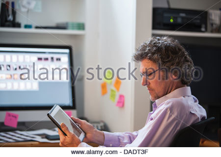 Male with digital tablet in front of computer screen - Stock Photo