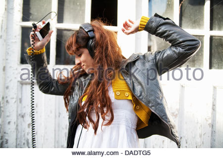 Young woman wearing headphones and dancing - Stock Photo