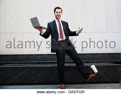 Businessman holding laptop and balancing coffee on his foot - Stock Photo