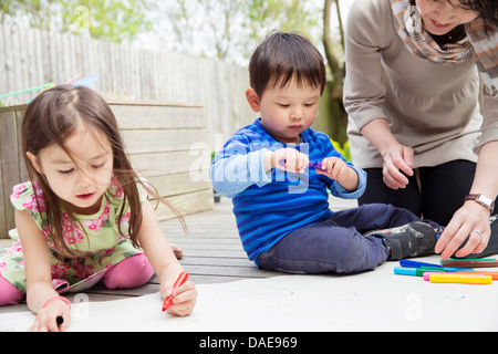 Mother and two children drawing in garden - Stock Photo