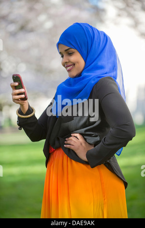 Portrait of young female in park looking at her mobile phone - Stock Photo