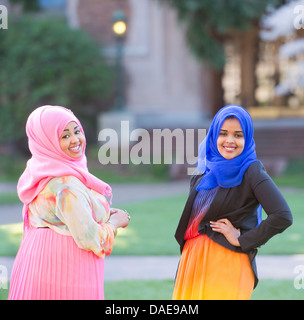 Portrait of two female friends in park wearing colorful headscarves - Stock Photo