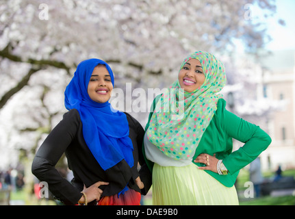 Portrait of two young females in park with hands on hips - Stock Photo