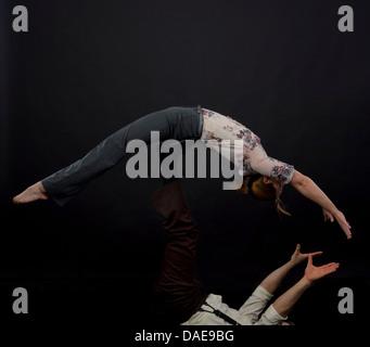 Studio shot of acrobats performing balancing trick - Stock Photo