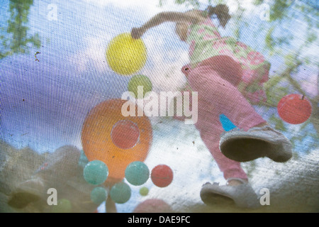 Young girls bouncing on garden trampoline - Stockfoto