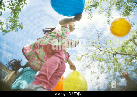 Young girls bouncing on garden trampoline with balloons - Stockfoto