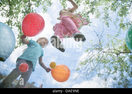 Young girls jumping on garden trampoline with balloons - Stockfoto