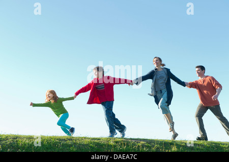 Parents and two children running and holding hands - Stock Photo