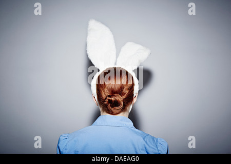Back view of young woman wearing bunny ears - Stock Photo