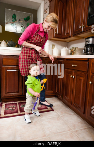 Young male toddler and grandmother in kitchen - Stock Photo