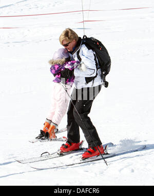 Crown Prince Willem-Alexander of The Netherlands (R) holds Princess Ariane in his arms as they stand on their skis - Stock Photo