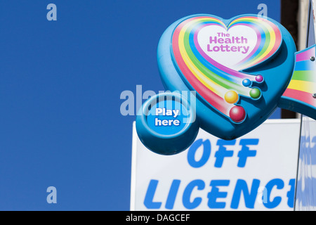 The Health Lottery sign against a blue sky on top a a off license sign - Stock Photo