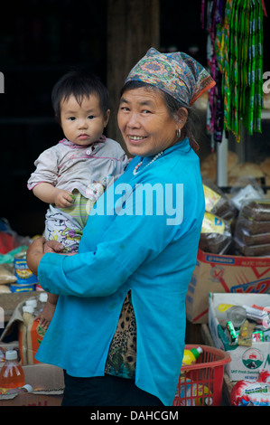 Hmong woman carrying child on her back. North of Bac Ha, Vietnam - Stock Photo