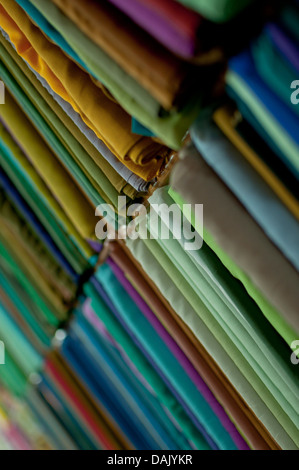 Fabrics lined up on a rack - Stock Photo
