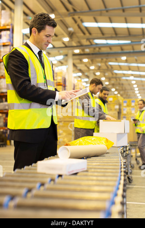 Workers checking packages on conveyor belt in warehouse - Stock Photo