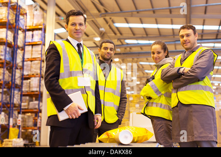 Businessman and workers smiling in warehouse - Stock Photo