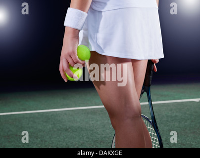 Tennis player holding balls on court - Stock Photo