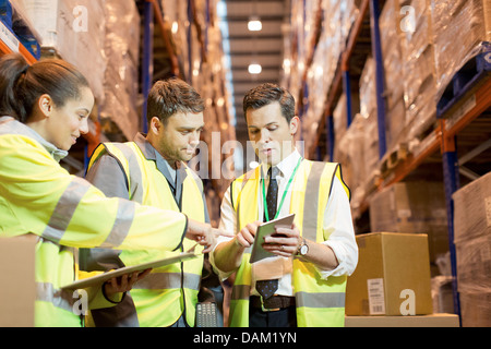 Businessman and workers talking in warehouse - Stock Photo