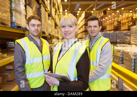 Businesswoman and workers smiling in warehouse - Stock Photo